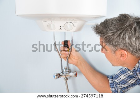 Close-up Of Mid-adult Male Plumber Repairing Water Heater