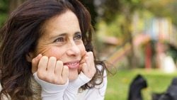 Close up of middle aged lovely brunette lady with hands on face with hopeful look in her eyes while resting in the park. Pretty mature woman, entrepreneur, positive thinking concepts