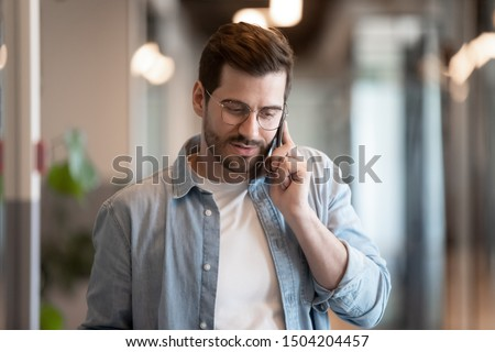 Close up of millennial businessman hold smartphone talking chatting using wireless connection in office, young male employee worker in glasses have pleasant cellphone call, use modern technology cell