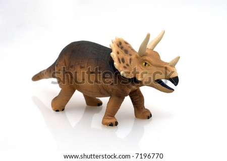 Close-up of miniature brown dinosaur toy on white background