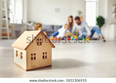 Close-up of miniature detached house on floor at home with happy family playing with little child in background. Mortgage, real estate business, buying property and confidence about future concepts
