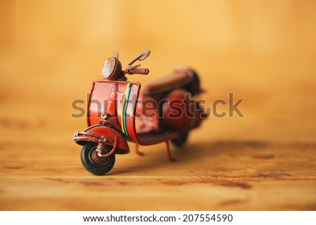 Close-up of miniature hand made toy motorcycle on rustic wooden background