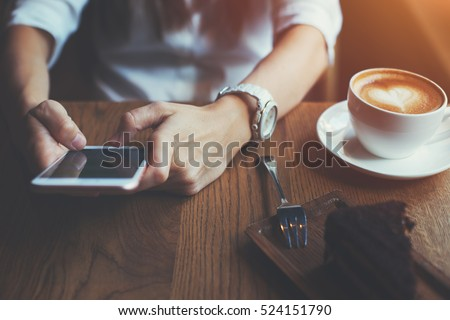 Close-up of mobile phone in woman's hands texting message, sitting in cafe with cup of coffee and cake #524151790