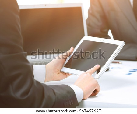 Close up of modern business-team using a tablet computer for work colleagues on the background #567457627