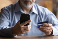 Close up of modern mature man hold cellphone and credit card make online payment or purchase form home. Smart senior male pay bills or shop on internet using smartphone. Elderly technology concept