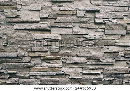 Close up of modern style design decorative uneven cracked real stone wall surface with cement, old vintage