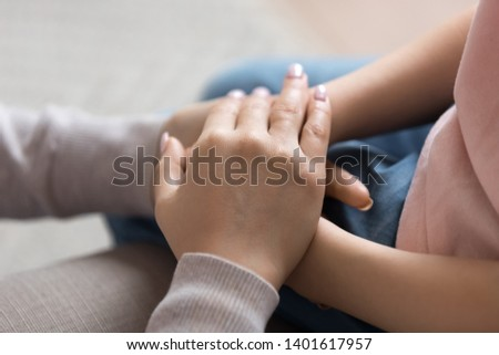Close up of mom support child hold little daughter hands show love and care, mother or nanny touch comfort small girl child make peace or reconcile after fight, parent and kid tender moment together