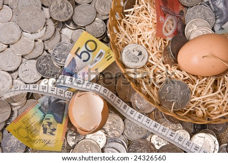 close up of money with eggs in nest with tape measure - australian currency notes and coins and tape measure