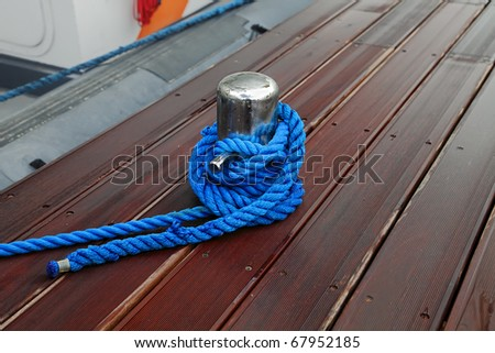Close-up of mooring bollard with blue rope in marina