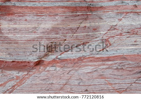 Close up of mostly red sediment layers in a rock formation. #772120816
