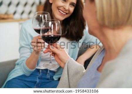 Close up of mother and adult daughter toasting in wine Foto stock ©