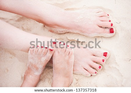Close up of mother and daughter feet on a tropical sandy beach