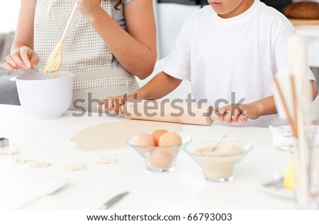 Close up of mother and son preparing a dough together in the kitchen