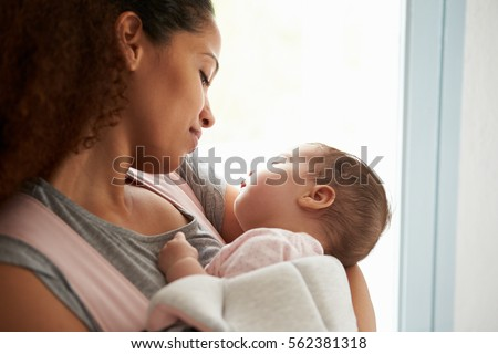 Close Up Of Mother Cuddling Baby Daughter At Home