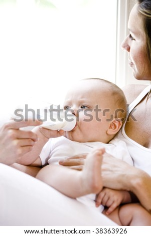 Close up of mother daydreaming while feeding bottle to baby