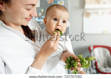 Close up of mother feeding her little baby with salad leaves during cooking lunch for whole family. Child looking aside and happily eats lettuce. #725707582
