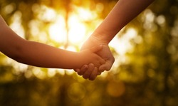 Close up of mother or older sister and a child hands at the sunset with copy space
