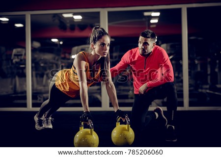 Photo of  Close up of motivated focused attractive young woman doing push ups exercise on the kettlebells in the gym with her handsome muscular personal trainer.