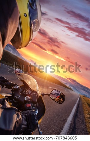 Close-up of motorcycle driver riding in Alpine highway. Outdoor photography, mountain landscape. Travel and sport photography. Speed and freedom concept #707843605