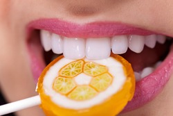 Close up of mouth with perfect teeth and lollipop