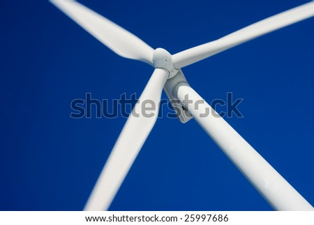 Close-up of moving wind turbine with deep blue sky