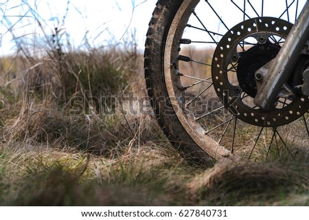 Close-up of muddy front wheel of dirt bike, details