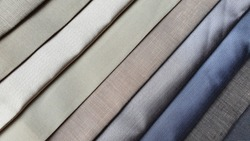 close up of multi cold color of silk fabric and linen samples. interior fabric material palette background. curtain or drapery samples.