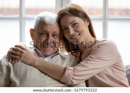 Close up of multi-generational relatives people family portrait concept. Loving caring grown up granddaughter hugs elderly 75s grandfather seated on sofa look at camera and smile capture lovely moment