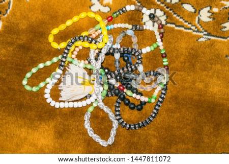 close up of multicolor muslim prayer beads on a prayer mate.multi color islamic prayer beads on ja e nmaz (prayer mate),brown background. #1447811072