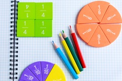 Close up of Multicolored math fractions, pencils on the open notepad on gray wooden table. Interesting math for kids background. Education, back to school concept