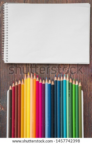 Close-up of multicolored pencil and white spiral note book on wooden desk #1457742398