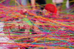 Close-up of multicolored tangled wool threads and yarn balls. People throw each other yarn balls during corporate game. Connection concept