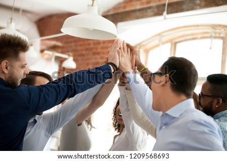 Close up of multiethnic colleagues give high five celebrating shared goal achievement or company success, excited diverse workers join hands engaged in teambuilding activity, show support and unity #1209568693
