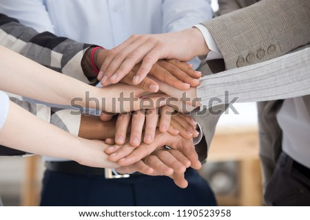 Close up of multiracial group of millennial business people or students standing stacking theirs hands palm together. Gesture sign of support unity and togetherness, starting common business concept
