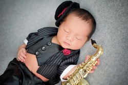 Close up of musician Newborn playing saxophone wearing black suite, black vest and tuxedo hat decorated with red rose. The baby sleeping on grey background.