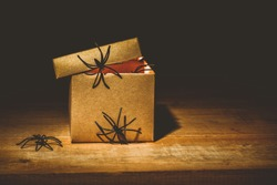 close-up of mysterious horror box on wooden table, with spiders climb around a box decoration idea, halloween concept