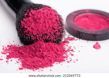 Close-up of  natural  black bristle of professional  make-up brush with crashed pink eyeshadow lying near opened single pink eyeshadow  pot  isolated on white background