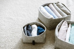 Close up of neatly folded and rolled clothes in baskets. Concept of tidiness, minimalism lifestyle and japanese t-shirt folding system. Minimalist capsule wardrobe and clothing organizing system