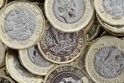 Close up of new British pound coins. Untidy pile of the new coins introduced in March 2017 that have several new security features to help prevent fraud.