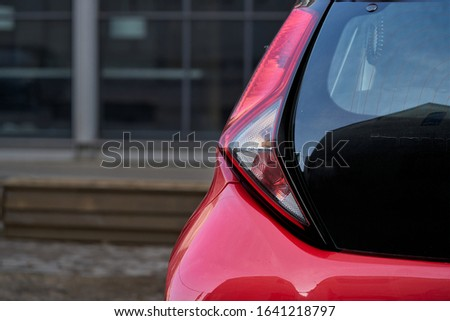 Close up of new red hatchback car parking on local road