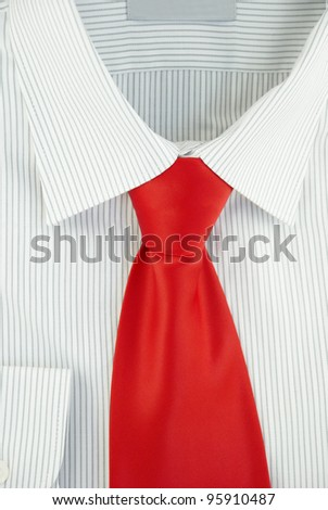 Close-up of new striped shirt with red silk necktie