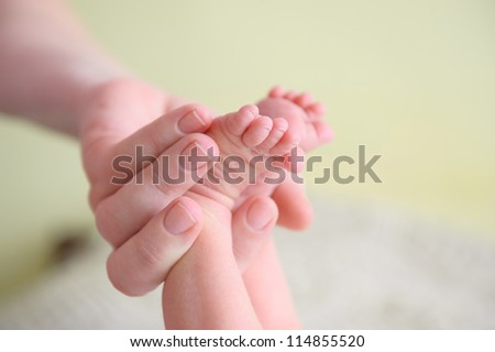 Close-up of newborn baby's feet in mothers hand