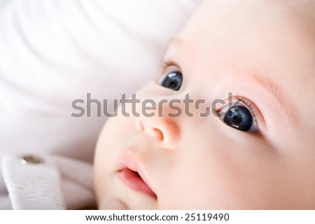 Close-up of newborn baby with blue eyes looking upwards surprisingly