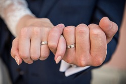 Close-up of newlyweds' hands wearing platinum wedding bands, with pinky fingers linked in gesture of unity and strength