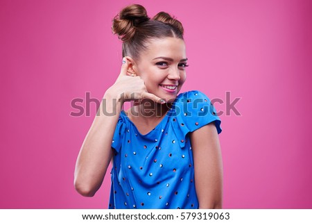 Close-up of nifty young girl making a call me gesture. Lovely female in blue dotted dress making a call me gesture isolated over pink background