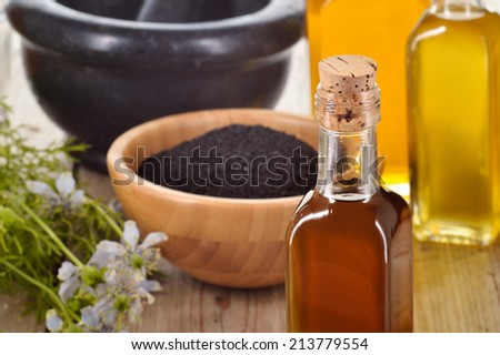 Close-up of nigella sativa oil in a bottle, against of nigella seeds and flowers on wooden background. Black cumin healing herb. Cold pressed, non refined oil. Traditional medicine. #213779554