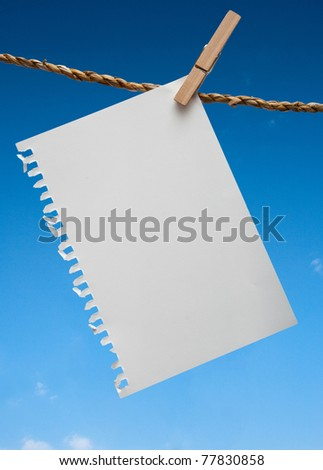 Close up of note paper and clothespins attached to a rope on blue sky background
