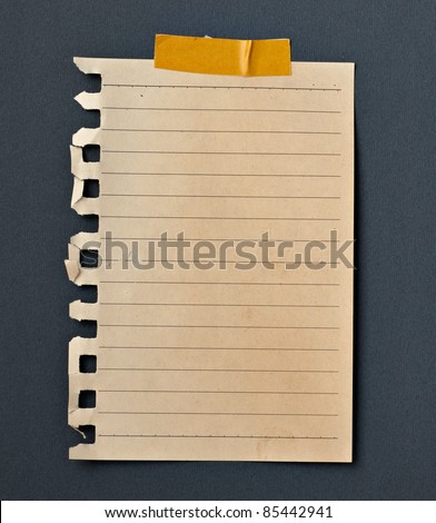 close up of note paper with adhesive tape on a black background
