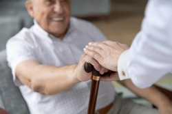 Close up of nurse caregiver palms covering hand of smiling senior patient holding cane. Sick old man struggle with trauma consequence make success on rehabilitation therapy with help support of doctor