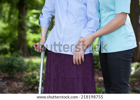 Close-up of nurse walking together with a female patient with a crutch